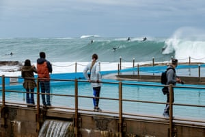 People watch surfers ride waves at Dee Why Point.