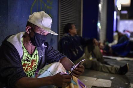 A man checks his phone outside a branch of Caixa Econômica Federal in Belo Horizonte.