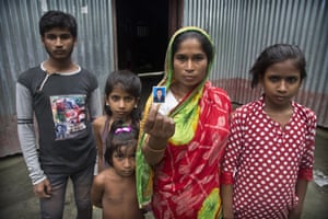 Halimun Nessa, 32, stands with her children and displays a photograph of her husband Rahim Ali, who committed suicide the day before his children were to appear in front of a NRC tribunal in Assam.