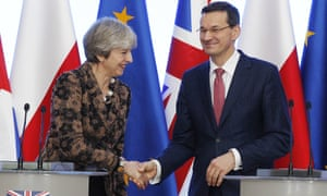 Polish Prime Minister Mateusz Morawiecki, right, and Britain's Prime Minister Theresa May shake hands during a press conference in Warsaw