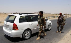 Afghan army soldiers search vehicles at a checkpoint on a highway leading to the Maiwind district of Kandahar.