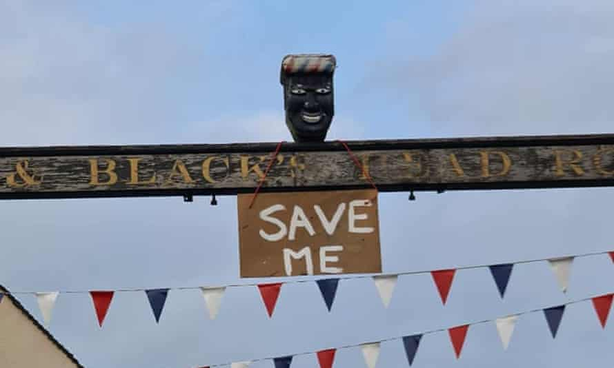 A 'Save Me' sign hangs from the controversial black head that stood in Ashbourne's town centre until last week.