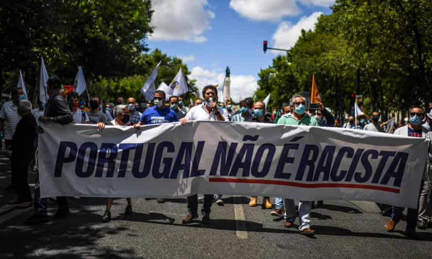"""André Ventura with banner reading """"Portugal is not racist"""""""