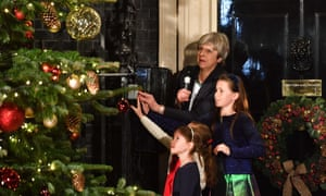 Theresa May is joined by some children to switch on the Downing Street Christmas tree lights