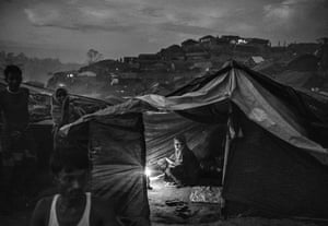 A woman uses a candle to light her tent at the Palongkali refugee camp
