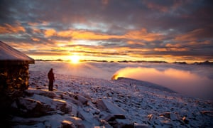 A lone figure at sunrise in a snowy landscape in Norway