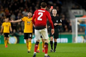Referee Martin Atkinson shows the red card to Victor Lindelhof of Manchester United.