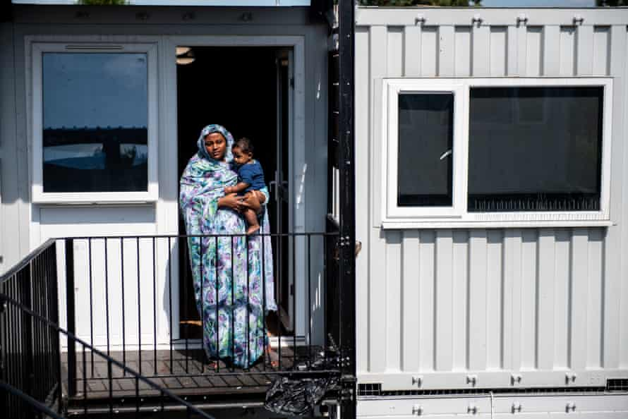 HANWELL, ENGLAND - AUGUST 23: Nasibah Yagoub, 21, poses for a photograph with her 7 month old son Youssef outside the front door to their accommodation at a development of converted shipping containers that are being used as social housing for homeless families on August 23, 2019 in Hanwell, England. Nasibah and her family were moved to one of the containers 6 months ago and is not happy about the accommodation. A new report from the children's commissioner for England has said that children growing up in such temporary housing are having their health and wellbeing put at risk. A number of temporary housing sites across Britain, including converted office blocks and shipping containers, have come under question in recent months. (Photo by Chris J Ratcliffe/Getty Images)