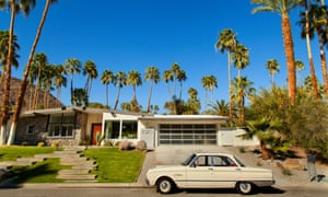1950s car parked outside a mid-century modernism design house on a sunny, blue-sky day in Palm Springs, California, US.