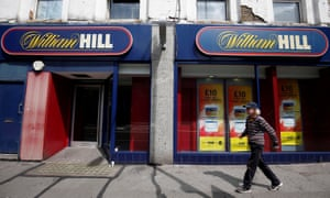 A pedestrian walks past a William Hill betting shop in London