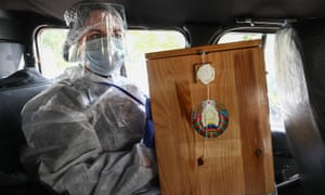 An election commission member holds a ballot box in a car before home voting.