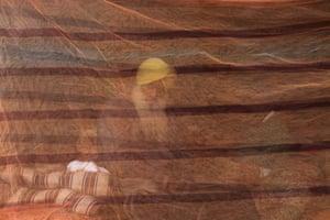 Delhi, India. A farmer sits behind a mosquito net at the Singhu border