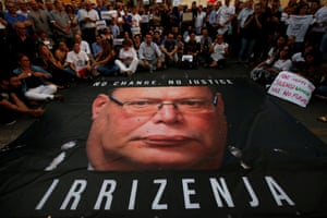 Coins are thrown on a banner calling for Malta police commissioner Lawrence Cutajar to resign during a protest over the assassination of journalist Daphne Caruana Galizia