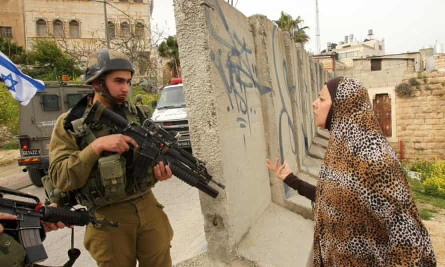 A Palestinian woman speaks with an Israeli soldier in Hebron, March 2016