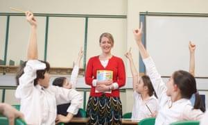 woman in classroom with children raising hands