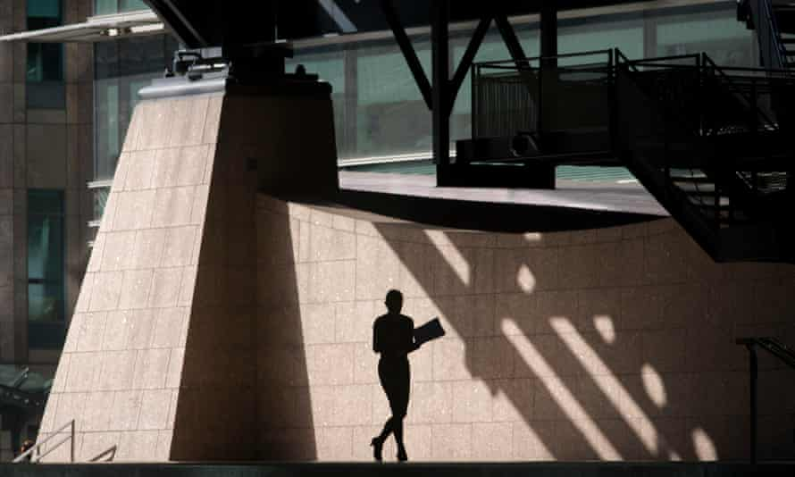 Silhouette of woman walking through the Broadgate corporate offices development in the City of London