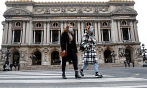 Women wearing masks walk past the closed Opera de Paris in the French capital