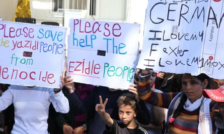 """Migrants hold signs reading """"Please help Yazidi people"""" as they wait for Pope Francis on the Greek island of Lesbos."""