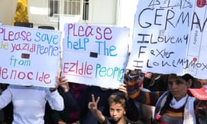 People hold signs reading 'Please help Yazidi people' during a visit of Pope Francis to Greece.