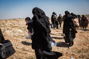 People who fled heavy fighting in the city of Baghuz walk towards a civilian screening point