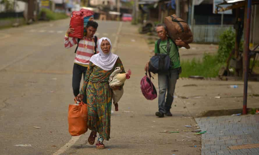 People carry their belongings in Marawi as they attempt to flee along a deserted street.