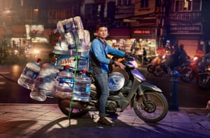 A delivery driver on a motorbike in Hanoi, Vietnam, carrying water for office workers