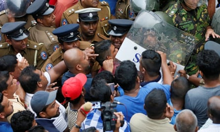 Supporters of Sri Lanka's newly appointed prime minister Mahinda Rajapaksa are pushed by members of the Special Task Force and the police in Colombo
