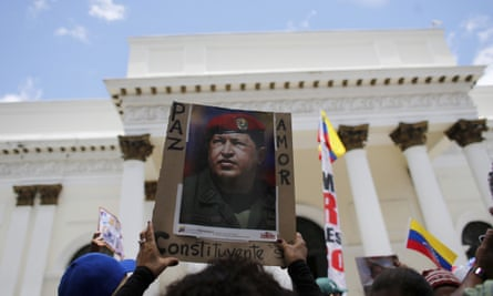 A supporter of Maduro holds up a poster of Chávez in Caracas. The country has faced increasing political turmoil.