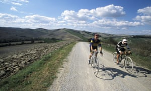 Two cyclists amid the countryside in Gaiole, Chianti, Tuscany, Italy.