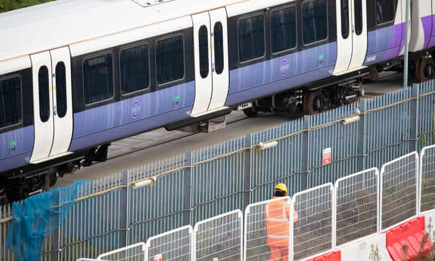 A worker wearing hi-vis clothing passes Crossrail trains at Old Oak Common, west London.