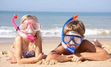 Girl and boy on beach wearing pink and blue snorkels