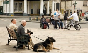 Elderly people and teenagers sitting in separate groups in Wallingford town centre in Oxfordshire, England