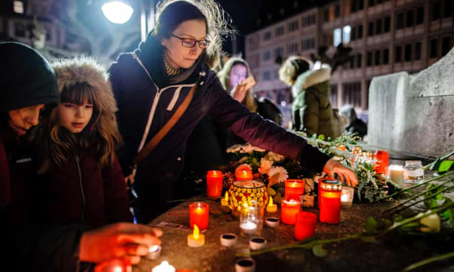Mourners place candles and flowers at the Unity Memorial at St Paul's church in Frankfurt am Main.