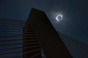 A solar eclipse shows through a layer of clouds over the Ravenel Bridge in Charleston, S.C. on Monday, Aug. 21, 2017. (Wade Spees/The Post And Courier via AP)