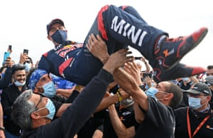 X-Raid Mini JCW Team's Stephane Peterhansel celebrates with teammates following his, and co-driver Edouard Boulanger's victory in the car category