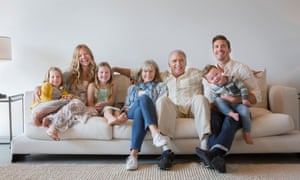 Multi-generation family sitting on sofa in living room
