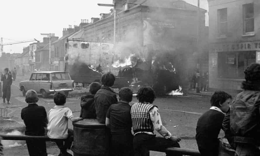 'Lots of people didn't want to know' … children watch hijacked vehicles burn following rioting in Belfast in 1976.