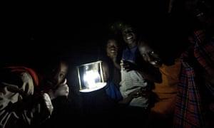 Children using an improvised solar-powered LED lamp in Kenya.