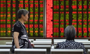 Women talk in front of a screen showing stock prices at a securities company in Beijing on 5 August.