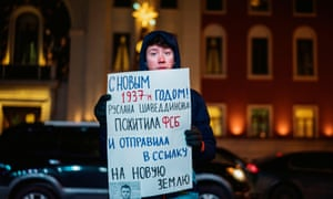 A man holds a poster reading 'Happy New Year 1937, Ruslan Shaveddinov has been kidnapped by the FSB (security service) and exiled to Novaya Zemlya' during a protest in central Moscow.