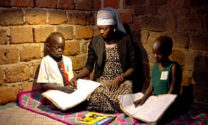 Children reading at night with the help of a solar system