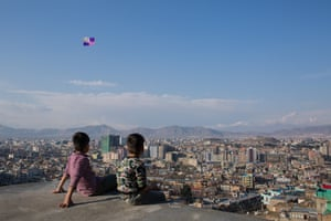 Children sitting on a rooftop watch kites fly above Kabul