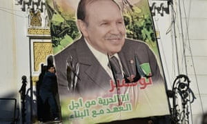 Algerian demonstrators tear down a large billboard depicting the country's president, Abdelaziz Bouteflika, on 22 February
