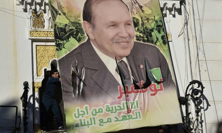 Algerian demonstrators tear down a large billboard depicting the country's president, Abdelaziz Bouteflika, on 22 February