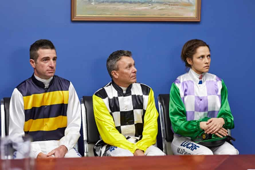 Two men and a woman in jockey colours sit against a wall