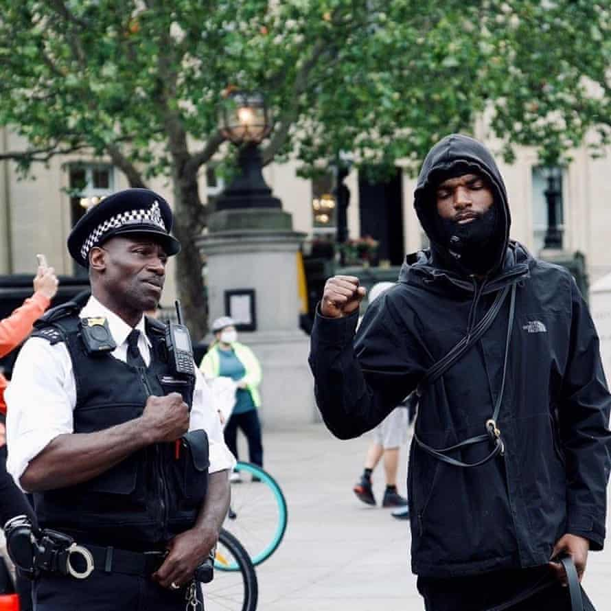 Faron with a police officer at the protest in London on Sunday.