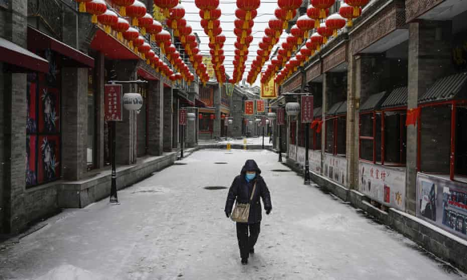 A Chinese woman wears a protective mask as she walks through in an empty and shuttered commercial street in Beijing.