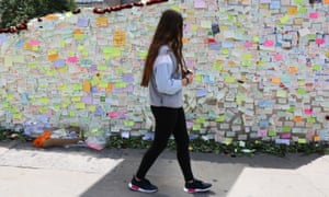 Girl walks past wall of Post-It notes