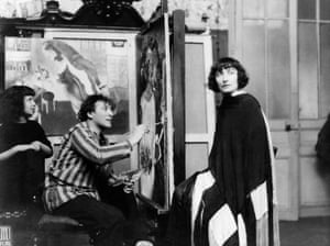 Chagall paints his wife, Bella, at his Paris atelier as his daughter, Ida, watches on. Behind him is Birthday.