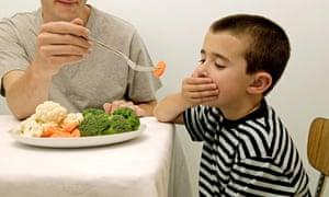 A boy sitting at a table with a plate full of vegetables and his hand over his mouth